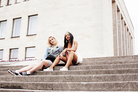 nations: Two teenage girls infront of university building smiling, having fun, lifestyle people concept, diverse nations