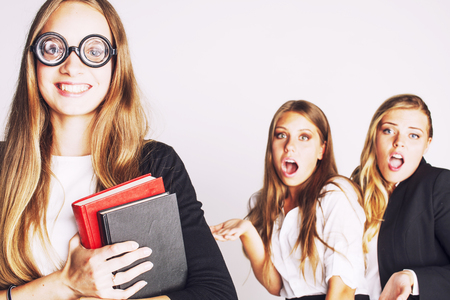 outsider: new student bookwarm in glasses against casual group on white, teen drama, lifestyle people concept close up