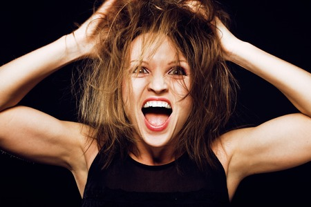 young silly crazy girl with messed hair making stupid faces on black background, lifestyle people concept close up Stock Photo