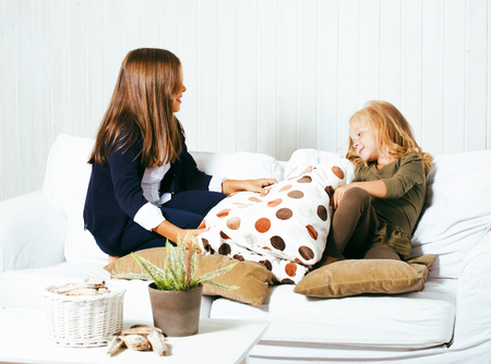 messing: two cute sisters at home playing, little smiling girl in house interior on sofa, messing hair, fighting with pillows, lifestyle people concept