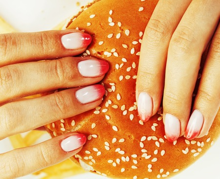 unhealthy lifestyle: woman hands with manicure holding hamburger and french fries isolated on white, food unhealthy lifestyle concept