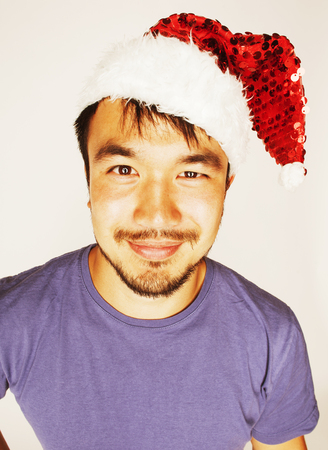 funy exotical asian Santa claus in new years red hat smiling on white background 스톡 콘텐츠