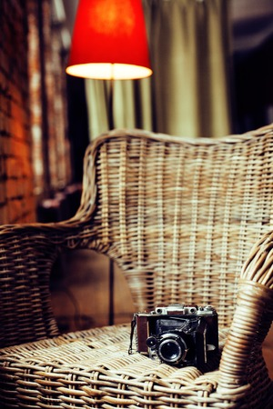 post card view. old fashion film camera in wooden chair, noone in cozy home interior close up Stock Photo