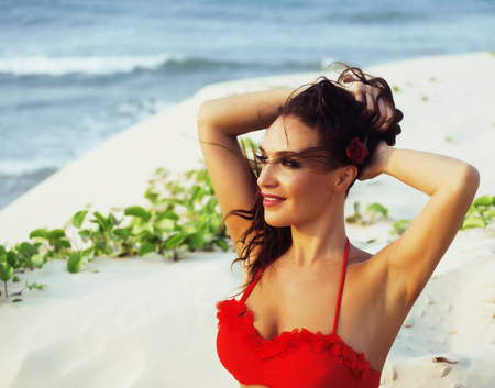 young pretty hispanic woman on seacoast with flying hair, hot sexy elegant portrait close up