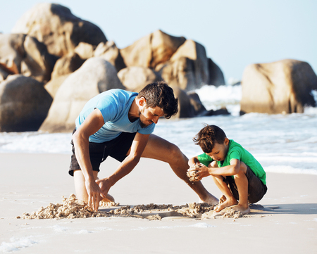 happy family on beach playing, father with son walking sea coast, rocks behind Stock Photo