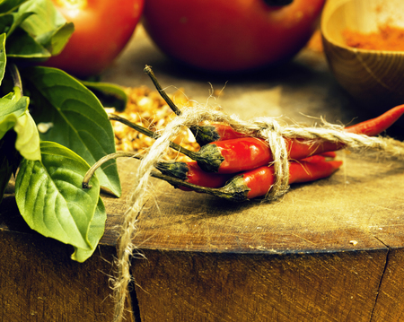 vegetables on wooden kitchen with spicies, tomato, chilli, green beans, garlic close up blurred background