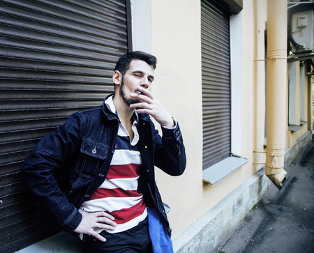 tough: middle age man smoking cigarette on bacyjard, stylish tough guy, lifestyle people concept close up