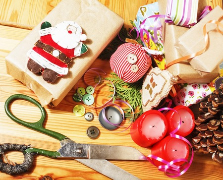 handmade christmas gifts in mess with toys, candles, fir, ribbon wooden vintage close up