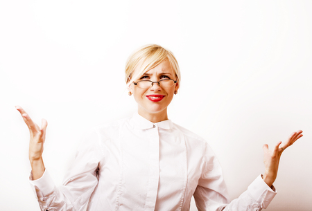 very emotional businesswoman in glasses, blond hair on white background. teacher hands up posing isolated. pointing gesturing, lifestyle people concept close up Stock Photo
