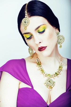 bridal makeup: young pretty caucasian woman like indian in ethnic jewelry close up on white, bridal makeup isolated
