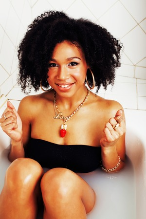 young afro-american teen girl laying in bath with foam, wearing swag jewelry flawless, making selfie, modern lifestyle concept close up Stock Photo