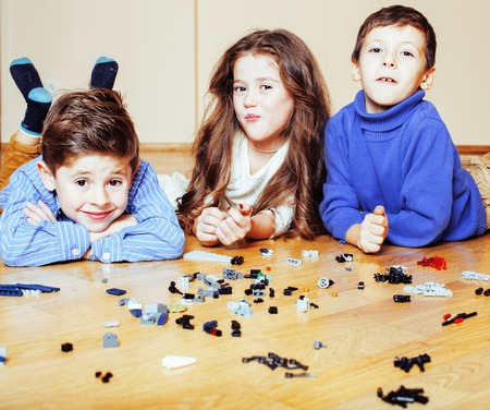 funny cute children playing lego at home, boys and girl smiling, first education role lifestyle close up Stock Photo