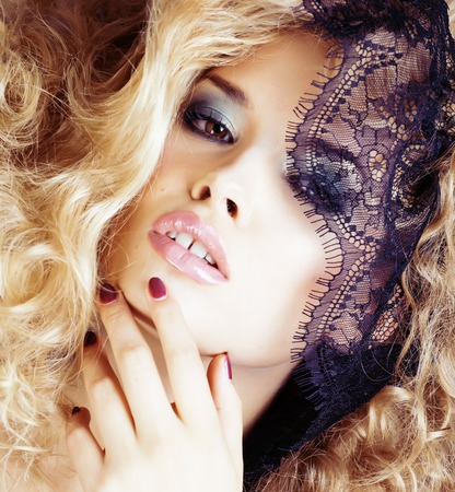 Portrait of beauty blond young woman through black lace close up sensual seduction manicure Stock Photo