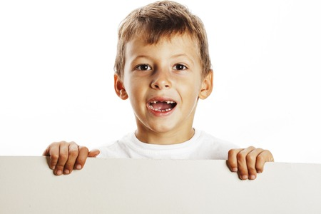little cute boy holding empty shit to copyspace isolated on white background close up gesturing smiling Stock Photo