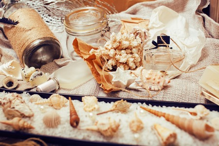 spa stuff: a lot of sea theme in mess like shells, candles, perfume, girl stuff on linen, pretty textured post card view vintage close up