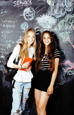 back to school after summer vacations, two teen real girls in classroom with blackboard painted together, lifestyle people concept Stock Photo