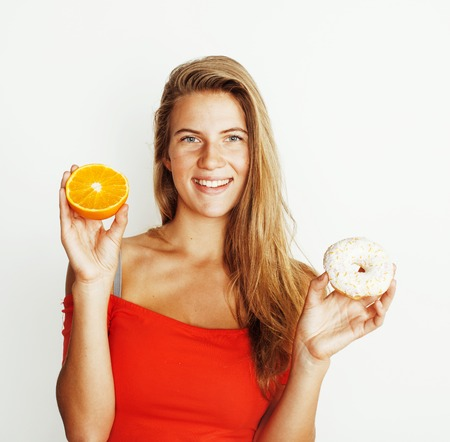 young blonde woman choosing between donut and orange fruit isolated on white background, lifestyle people concept close up