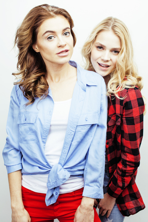 jeune fille adolescente: two pretty blond woman having fun together on white background, mature mother and young teenage daughter, lifestyle people concept close up Banque d'images