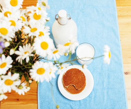 Simply stylish wooden kitchen with bottle of milk and glass on table, summer flowers camomile, healthy foog moring concept noone close up Stock Photo