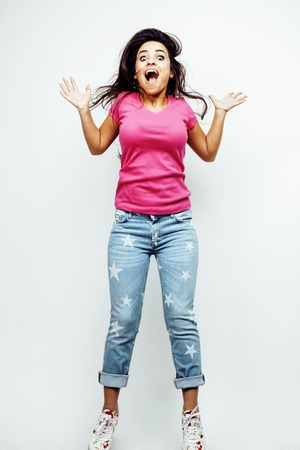 young happy smiling latin american teenage girl emotional posing on white background, jumping flying in joy, lifestyle people concept close up Stock Photo