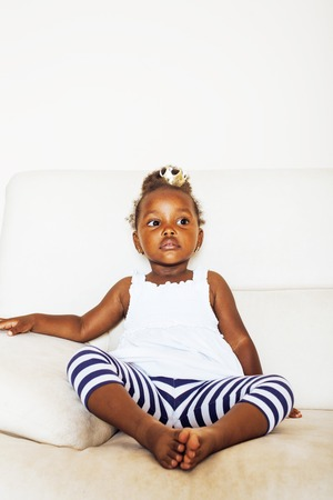 little pretty african american girl sitting in white chair wearing toy crown on head like princess or queen, lifestyle people concept close up Stock Photo