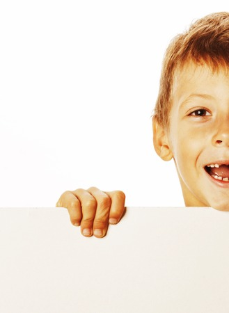 normal school: little cute boy holding empty shit to copyspace isolated on white background close up gesturing smiling Stock Photo