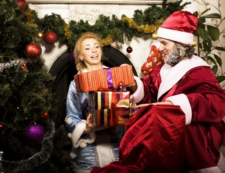 portrait of Santa Claus with Snow Maiden at Cristmas tree holding gifts at fire place, lifestyle holiday people close up Stock Photo