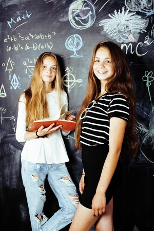normal school: back to school after summer vacations, two teen real girls in classroom with blackboard painted together, lifestyle people concept Stock Photo
