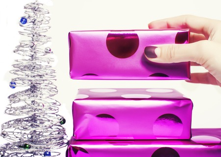 christmas manicure: woman manicured hand puting christmas gift to rest pile of purple gifts close up isolated silver little tree cute stylish manicure, hand putting gift box, womans finger