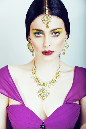 bridal makeup: young pretty caucasian woman like indian in ethnic jewelry close up on white, bridal makeup