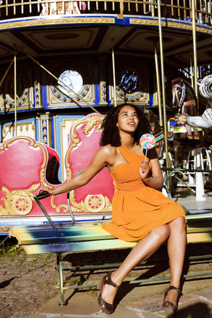adolescencia: fresco adolescente afroamericano real con caramelo cerca de los carruseles en el parque de atracciones, las personas de estilo de vida concepto