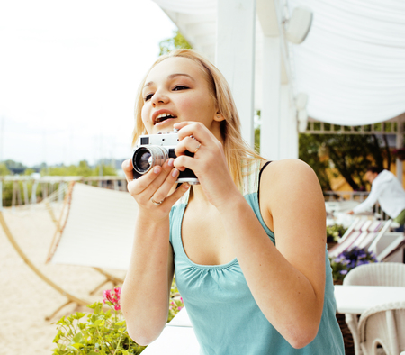 street shot: young cute teenage girl with camera outside, adorable photograph Stock Photo