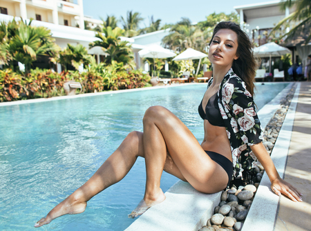 young pretty woman at swimming pool relaxing in chair, fashion l