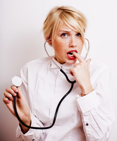 funny doctor with stethoscope, smiling blond woman medical equipment showing on white background