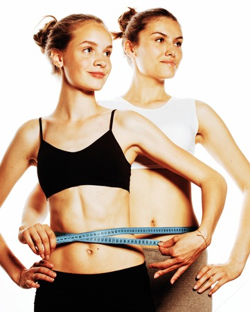 taping: two sport girls measuring themselves isolated on white