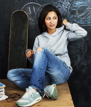 normal school: young cute teenage girl in classroom at blackboard seating on ta Stock Photo