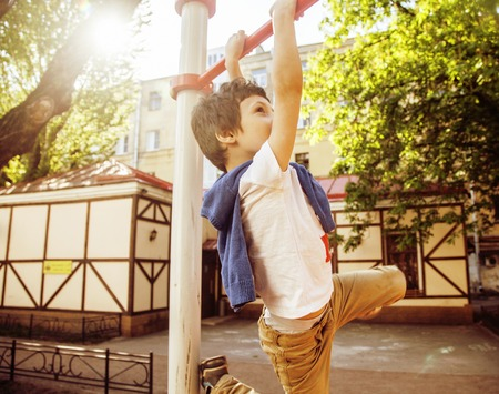 normal school: little cute blond boy hanging on playground outside, alone training with fun, lifestyle children concept Stock Photo