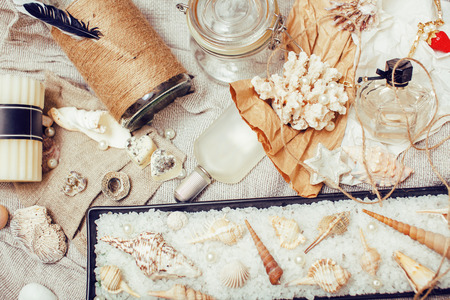 spa stuff: a lot of sea theme in mess like shells, candles, perfume, girl stuff on linen, pretty textured post card view vintage