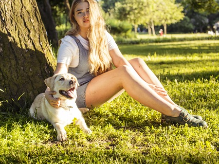 poquito: young attractive blond woman playing with her dog in green park at summer, lifestyle people concept