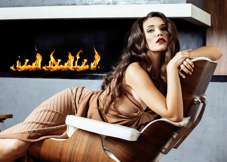 fireplace home: beauty yong brunette woman sitting near fireplace at home Stock Photo