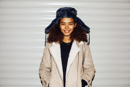 bum: young pretty african american girl teenage outside on street, looking like real junky, social issues concept, red eyes, bum stupid hat, fashion hipster lifestyle people close up