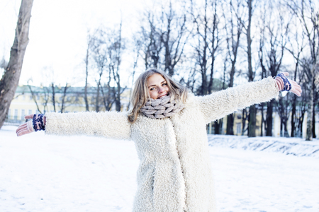 young pretty teenage hipster girl outdoor in winter snow park having fun drinking coffee, warming up happy smiling, lifestyle people concept Stock Photo