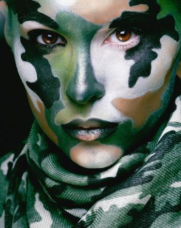 Schöne junge Mode Frau mit militärischen Stil Kleidung und Gesicht malen Make-up, khaki Farben