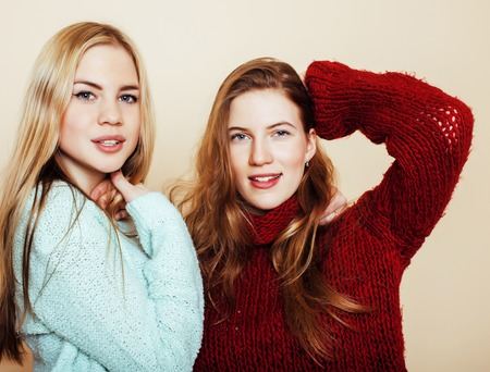 Two young girlfriends in winter sweaters indoors having fun. Lif