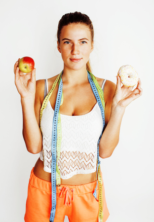 young blonde woman choosing between donut and apple fruit isolated on white background, lifestyle people concept, measuring tape for diet