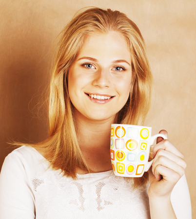 habbit: young cute blond girl drinking coffee close up on warm brown bac