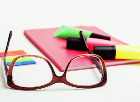 business, education and technology concept - close up of notebook, paper stickers, glasses, pencil different new stuff on white background macro