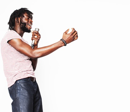 rapping: young handsome african american boy singing emotional with microphone isolated on white background, in motion gesturing smiling, lifestyle people concept Stock Photo