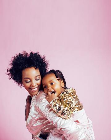若いかなり幸せなライフ スタイルの現代人のコンセプト、ピンクの背景の笑顔を抱いて、少しかわいい娘とアフリカ系アメリカ人の母
