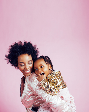 young pretty african-american mother with little cute daughter hugging, happy smiling on pink background, lifestyle modern people concept